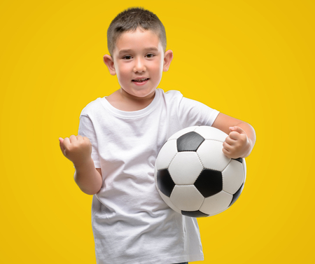 Dark haired little child playing with soccer ball screaming proud and celebrating victory and success very excited, cheering emotion Archivio Fotografico
