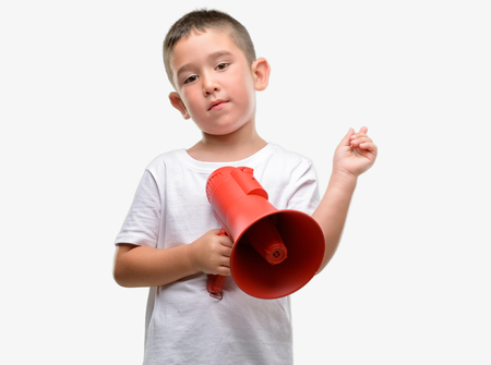 Dark haired little child holding megaphone very happy pointing with hand and finger to the side