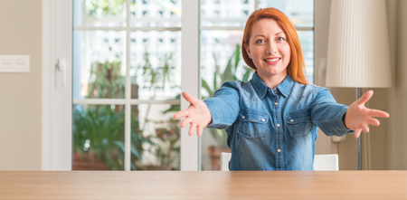 Redhead woman at home looking at the camera smiling with open arms for hug. Cheerful expression embracing happiness.