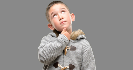 Dark haired little child wearing a coat serious face thinking about question, very confused idea