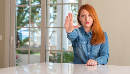 Redhead woman at home with open hand doing stop sign with serious and confident expression, defense gesture