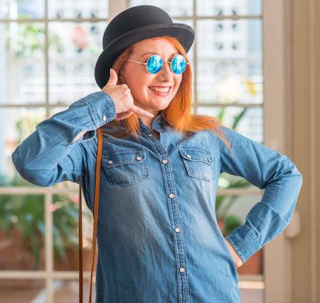 Stylish redhead woman wearing bowler hat and sunglasses smiling doing phone gesture with hand and fingers like talking on the telephone. Communicating concepts.