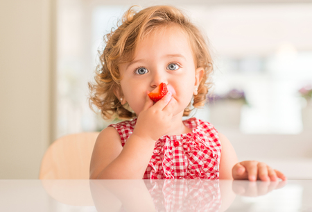 Beautiful blonde child  blue eyes eating strawberry at home.