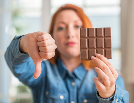 Redhead woman holding chocolate bar at home with angry face, negative sign showing dislike with thumbs down, rejection concept