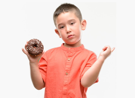 Dark haired little child eating doughnut very happy pointing with hand and finger to the side Archivio Fotografico