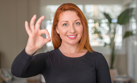 Redhead woman at home doing ok sign with fingers, excellent symbol