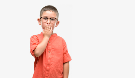 Dark haired little child wearing glasses cover mouth with hand shocked with shame for mistake, expression of fear, scared in silence, secret concept