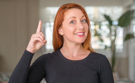 Redhead woman at home surprised with an idea or question pointing finger with happy face, number one Archivio Fotografico