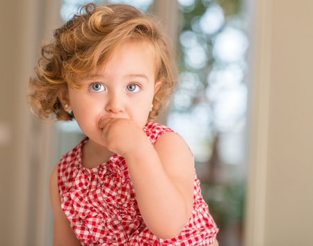 Beautiful blonde child with blue eyes eating candy at home.