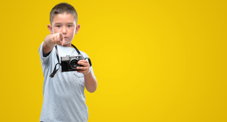 Dark haired little child holding vintage camera pointing with finger to the camera and to you, hand sign, positive and confident gesture from the front