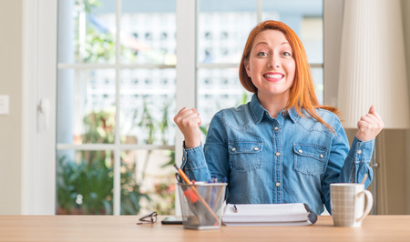 Redhead woman studying at home screaming proud and celebrating victory and success very excited, cheering emotion