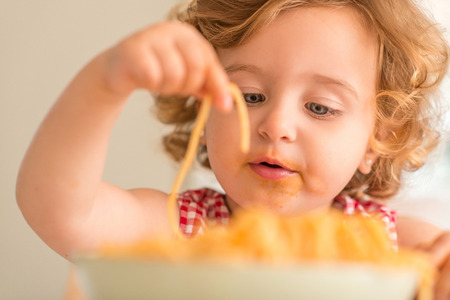 Close up of beautiful blond child eating spaghetti with hands at home. Archivio Fotografico
