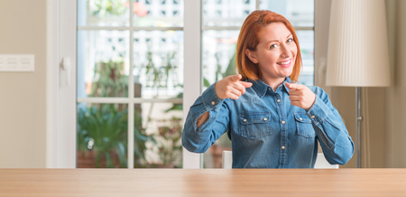 Redhead woman at home pointing fingers to camera with happy and funny face. Good energy and vibes.