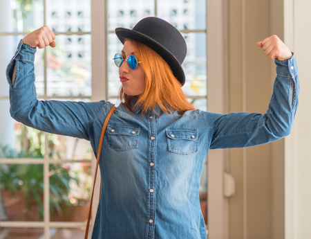 Stylish redhead woman wearing bowler hat and sunglasses showing arms muscles smiling proud. Fitness concept.