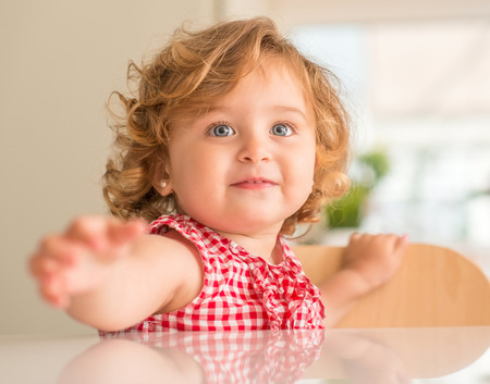 Beautiful blond child smiling asking for hold, wanting attention at home.