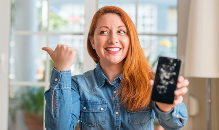 Redhead woman holding broken smartphone pointing with hand and finger up with happy face smiling