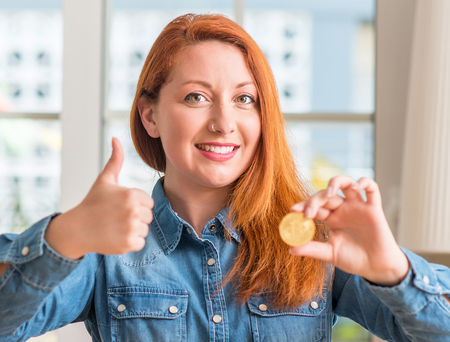 Redhead woman holding bitcoin cryptocurrency at home happy with big smile doing ok sign, thumb up with fingers, excellent sign