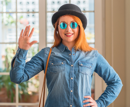 Stylish redhead woman wearing bowler hat and sunglasses showing and pointing up with fingers number five while smiling confident and happy.