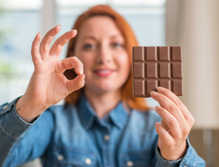 Redhead woman holding chocolate bar at home doing ok sign with fingers, excellent symbol