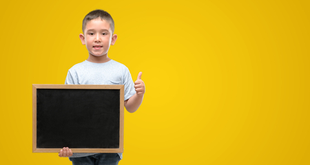 Dark haired little child holding a blackboard happy with big smile doing ok sign, thumb up with fingers, excellent sign