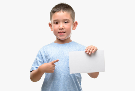 Dark haired little child holding a blank card very happy pointing with hand and finger