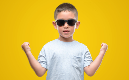 Dark haired little child wearing sunglasses screaming proud and celebrating victory and success very excited, cheering emotion