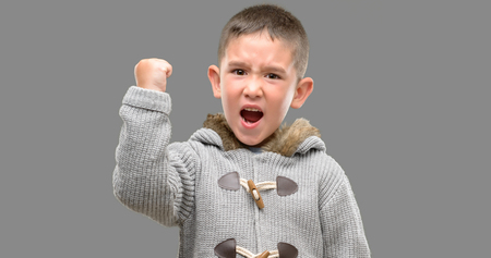 Dark haired little child wearing a coat annoyed and frustrated shouting with anger, crazy and yelling with raised hand, anger concept