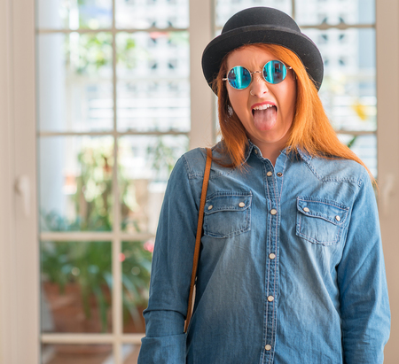 Stylish redhead woman wearing bowler hat and sunglasses sticking tongue out happy with funny expression. Emotion concept.