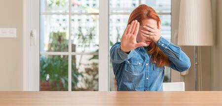 Redhead woman at home covering eyes with hands and doing stop gesture with sad and fear expression. Embarrassed and negative concept.