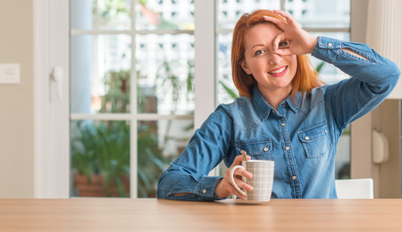 Redhead woman holding a cup of coffee with happy face smiling doing ok sign with hand on eye looking through fingers Archivio Fotografico