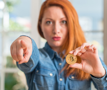 Redhead woman holding bitcoin cryptocurrency at home pointing with finger to the camera and to you, hand sign, positive and confident gesture from the front Фото со стока
