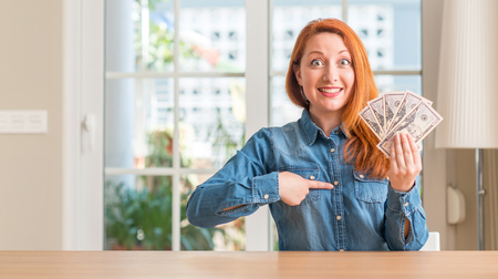 Redhead woman holding dollar bank notes at home with surprise face pointing finger to himself
