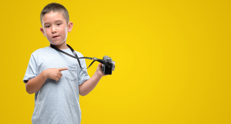 Dark haired little child holding vintage camera very happy pointing with hand and finger to the side