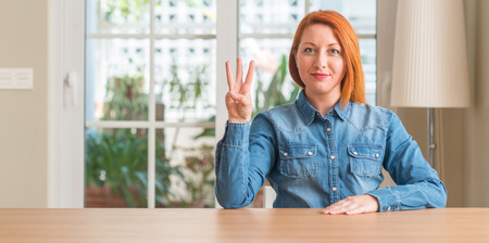 Redhead woman at home showing and pointing up with fingers number three while smiling confident and happy. Archivio Fotografico