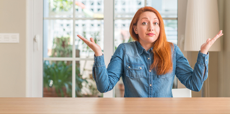 Redhead woman at home clueless and confused expression with arms and hands raised. Doubt concept.