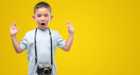 Dark haired little child holding vintage camera scared in shock with a surprise face, afraid and excited with fear expression