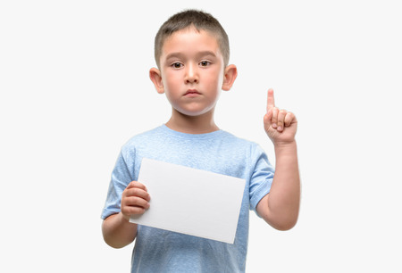 Dark haired little child holding a blank card surprised with an idea or question pointing finger with happy face, number one Stock fotó