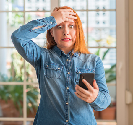Redhead woman using smartphone at home stressed with hand on head, shocked with shame and surprise face, angry and frustrated. Fear and upset for mistake.