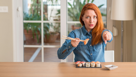 Redhead woman eating sushi using chopsticks pointing with finger to the camera and to you, hand sign, positive and confident gesture from the front Archivio Fotografico