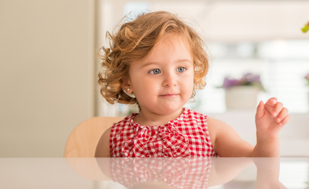 Beautiful blonde child with blue eyes sitting at home. Фото со стока