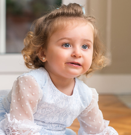 Beautiful and happy blond child in a dress sitting on the floor at home. Close up.