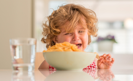 Beautiful blond child eating spaghetti with hands crying with tantrum at home. Archivio Fotografico