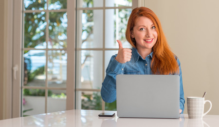 Redhead woman using computer laptop at home happy with big smile doing ok sign, thumb up with fingers, excellent sign