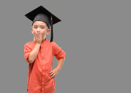 Dark haired little child wearing graduation cap cover mouth with hand shocked with shame for mistake, expression of fear, scared in silence, secret concept