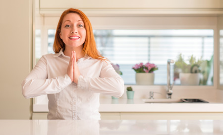 Redhead woman at kitchen praying with hands together asking for forgiveness smiling confident.