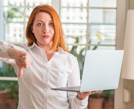 Redhead woman using computer laptop at home with angry face, negative sign showing dislike with thumbs down, rejection concept Stock Photo