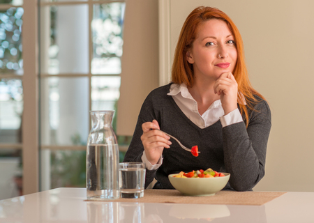 Redhead woman eating fruit bowl, kiwi and strawberry at home serious face thinking about question, very confused idea