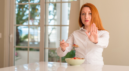 Redhead woman eating cereals with raspberries at home with open hand doing stop sign with serious and confident expression, defense gesture