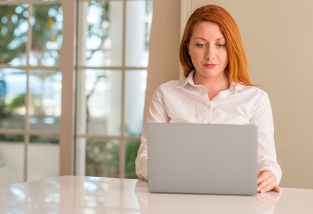 Redhead woman using computer laptop at home with a confident expression on smart face thinking serious Stock Photo