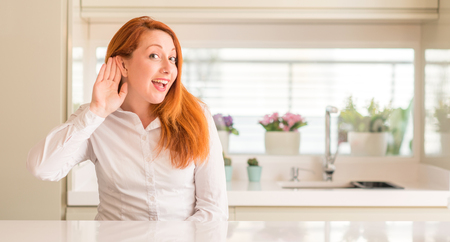 Redhead woman at kitchen smiling with hand over ear listening an hearing to rumor or gossip. Deafness concept.